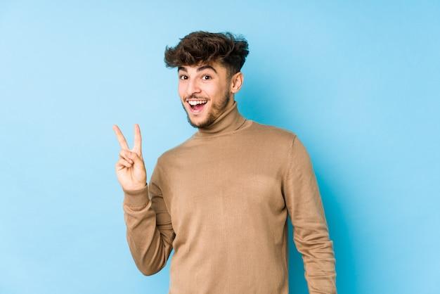 Junger arabischer mann lokalisiertes frohes und sorgloses zeigen eines friedenssymbols mit den fingern.
