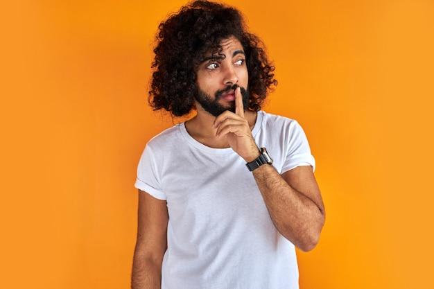 Junger arabischer mann mit dem lockigen schwarzen haar, das seinen finger auf der vorderseite seines mundes hebt und bittet, ruhig zu sein
