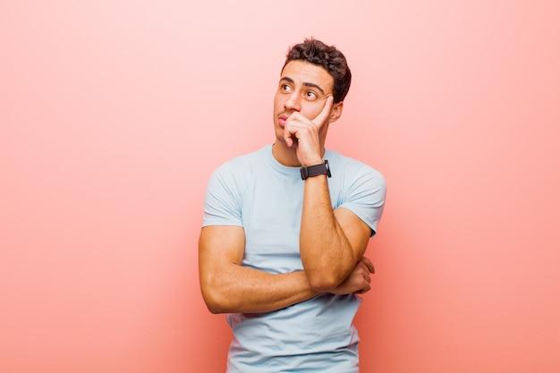 Junger arabischer mann mit einem konzentrierten blick, der sich mit einem zweifelhaften ausdruck wundert, aufblickend und zur seite gegen rosa wand schauend