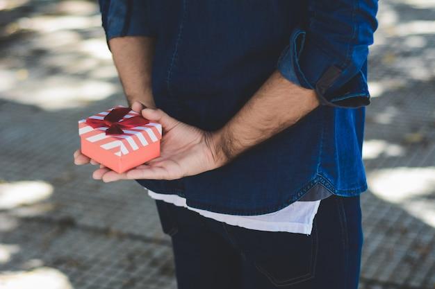 Junger arabischer mann mit einer roten geschenkbox
