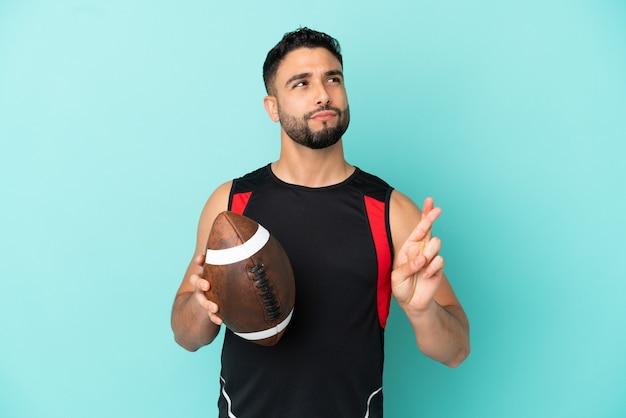 Junger arabischer mann spielt rugby isoliert auf blauem hintergrund mit gekreuzten fingern und wünscht das beste