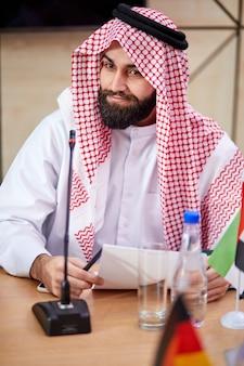 Junger arabischer scheichmann, der traditionelle emiratskleidung trägt, sitzt am schreibtisch auf geschäftstreffen, männlicher saudi-arabischer arabischer geschäftsmuslim traditioneller scheich, der aufwirft