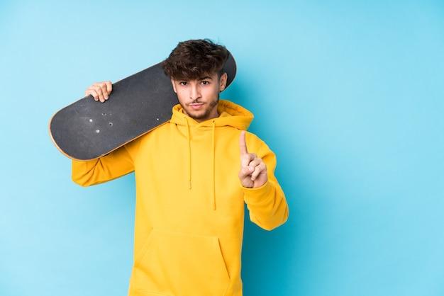 Junger arabischer skatermann isoliert, der nummer eins mit finger zeigt.