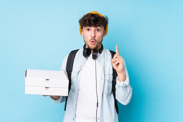 Junger arabischer studentenmann, der pizzas isoliert hält, die einige große idee, konzept der kreativität haben.