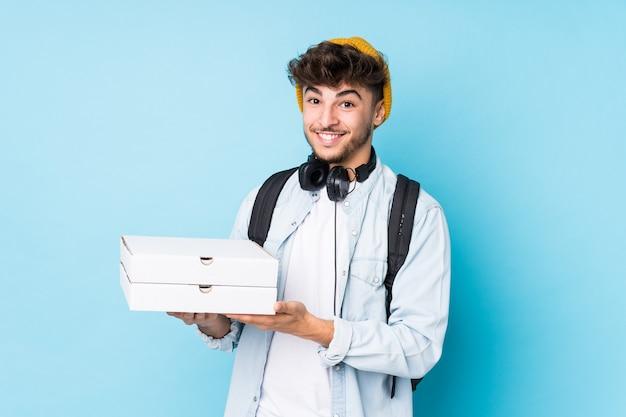 Junger arabischer studentenmann, der pizzas isoliert lacht und spaß hat.