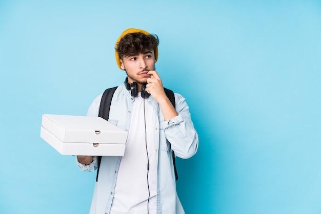 Junger arabischer studentenmann, der pizzen lokalisiert entspanntes denken über etwas betrachtet, das einen kopienraum betrachtet.