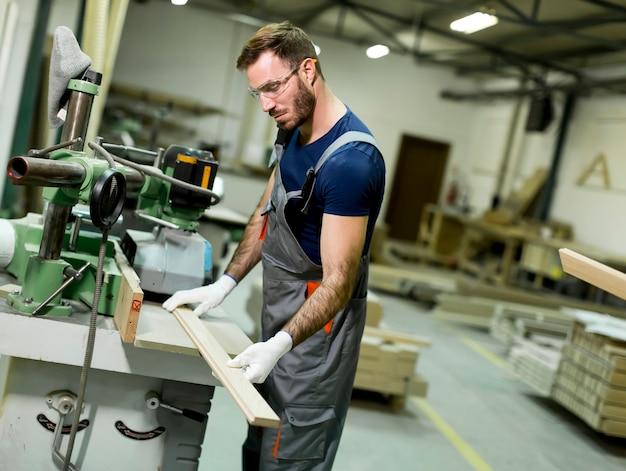 Junger arbeiter arbeitet in einer fabrik für die produktion von möbeln