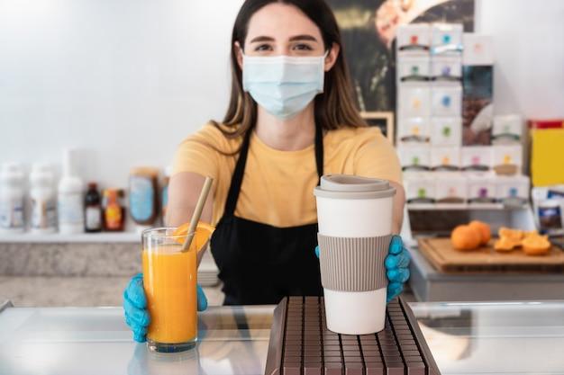 Junger arbeiter, der dem kunden im restaurant eine bestellung zum mitnehmen liefert, während er eine gesichtsmaske trägt
