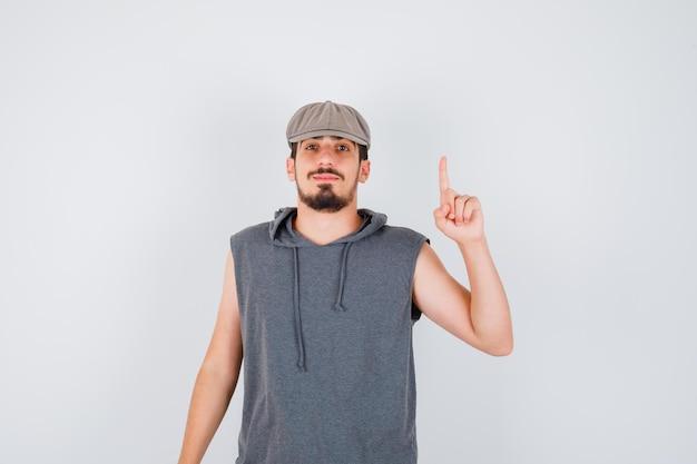Junger arbeiter, der den zeigefinger in der heureka-geste in grauem t-shirt und mütze hebt und ernst aussieht