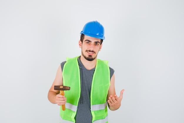 Junger arbeiter, der eine axt in einer hand hält, während er die andere hand streckt, während er etwas in bauuniform hält und glücklich aussieht