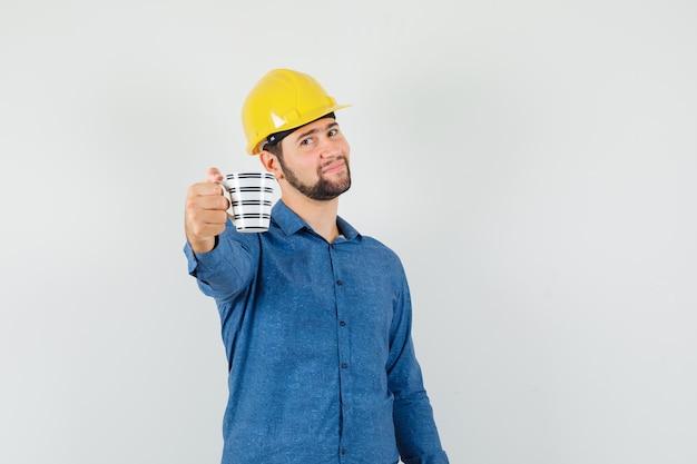 Junger arbeiter, der eine tasse kaffee im hemd, im helm anbietet und sanft aussieht