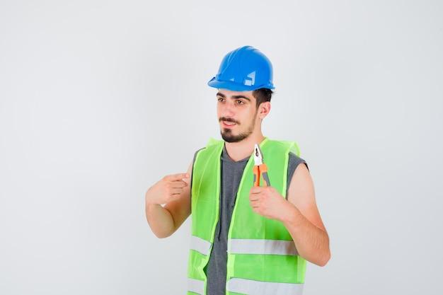 Junger arbeiter, der eine zange hält und darauf in bauuniform zeigt und glücklich aussieht