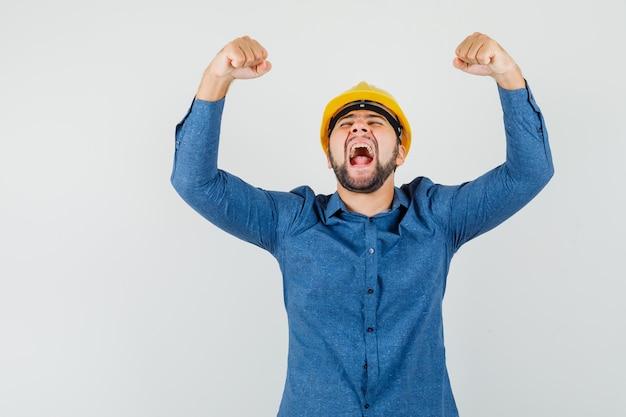 Junger arbeiter, der erfolgsgeste zeigt, während er in hemd, helm schreit und glückselig aussieht