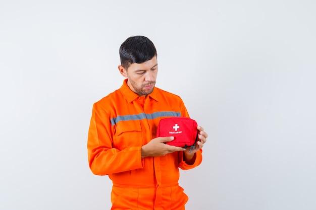 Junger arbeiter, der erste-hilfe-kit in einheitlicher vorderansicht hält.