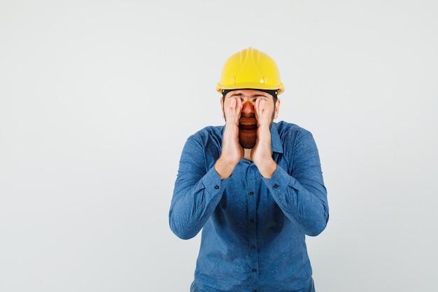 Junger arbeiter, der geheimnis mit händen nahe offenem mund in hemd, helm erzählt