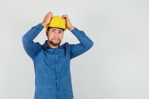 Junger arbeiter, der hände auf kopf in hemd, helm hält und hilflos schaut.