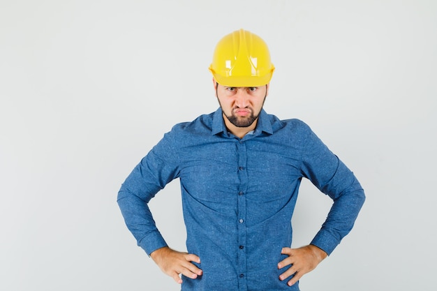 Junger arbeiter, der hände auf taille im hemd, im helm hält und wütend schaut