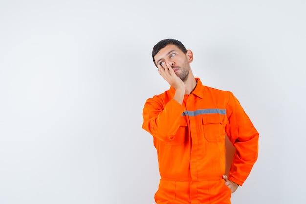 Junger arbeiter, der hand auf gesicht in uniform hält und traurig aussieht.