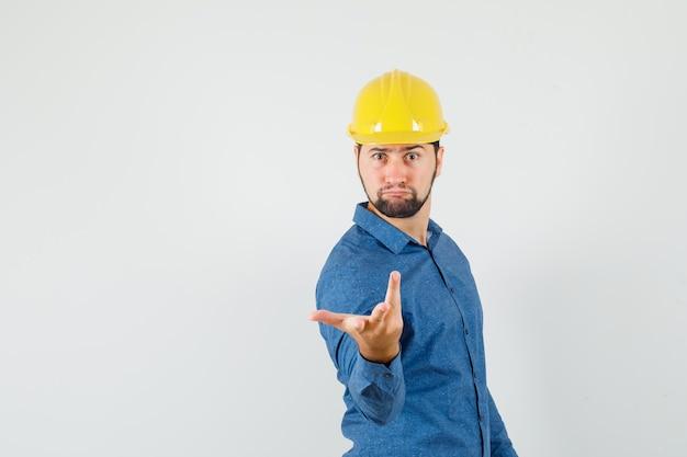 Junger arbeiter, der hand in verwirrter geste in hemd, helm streckt