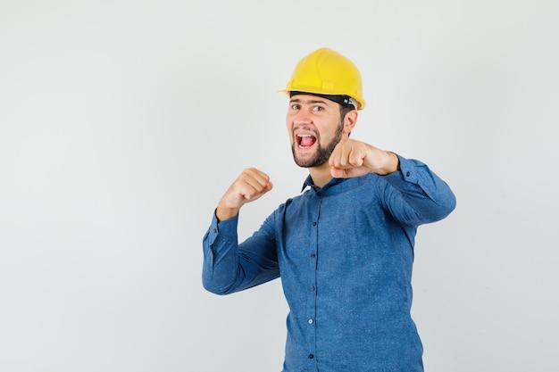 Junger arbeiter, der im kampf steht, posiert im hemd, im helm und schaut munter.