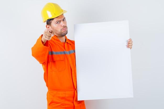 Junger arbeiter, der leere leinwand hält und vorne in uniform, helm zeigt.
