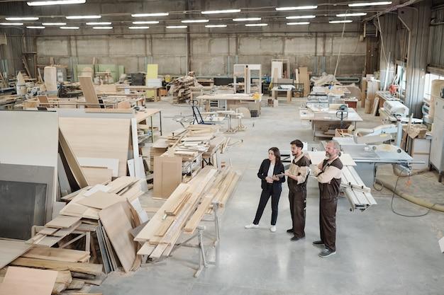Junger arbeiter der möbelfabrik in uniform, die weiblichen manager in der neuen ausrüstung der abendgarderobe beim arbeitstreffen im lager zeigt