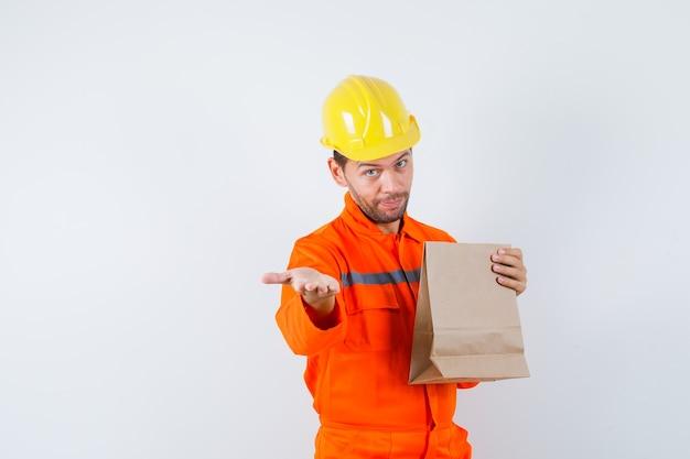 Junger arbeiter, der papiertüte hält und hand in uniform streckt.