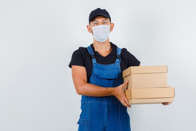 Junger arbeiter, der pappkartons in uniform, maskenvorderansicht hält.
