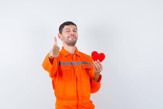 Junger arbeiter, der rotes herz hält, daumen in uniform zeigt und erfreut aussieht.