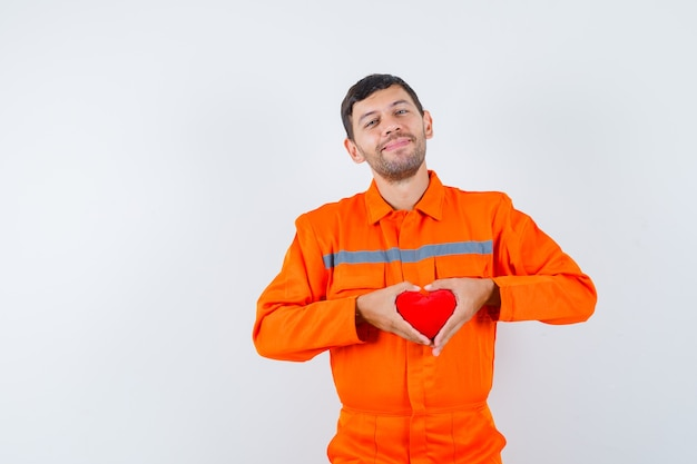 Junger arbeiter, der rotes herz in uniform hält und fröhlich schaut.