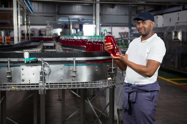 Junger arbeiter, der saftflasche in der fabrik inspiziert