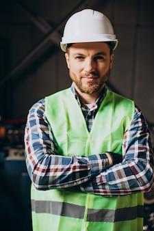 Junger arbeiter, der weißen schutzhelm trägt