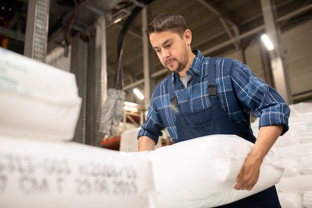 Junger arbeiter der zeitgenössischen polymerproduktionsfabrik, der säcke mit kunststoffgranulat vor der verarbeitung lädt