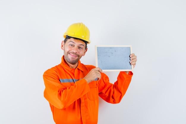 Junger arbeiter hält tafel in uniform, helm und sieht fröhlich aus.