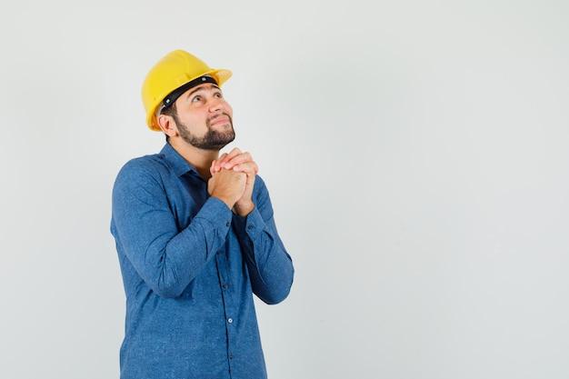 Junger arbeiter im hemd, helm, der hände in der gebetsgeste fasst und hoffnungsvoll aussieht