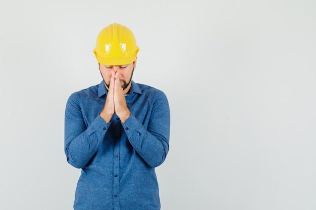 Junger arbeiter im hemd, helm, der hände in der gebetsgeste hält und ruhig schaut