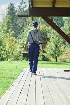 Junger arbeiter in blauen overalls mit werkzeugkasten nach reparaturarbeiten im cottage-haus