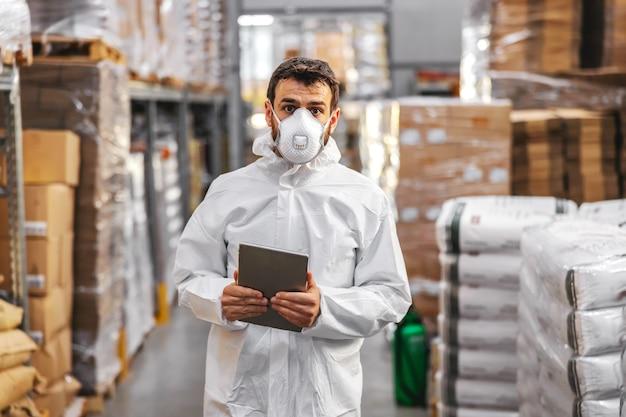 Junger arbeiter in der schutzuniform mit gesichtsmaske, die tablette hält und warengehalt beim stehen im lager überprüft. konzept des corona-virus-ausbruchs.