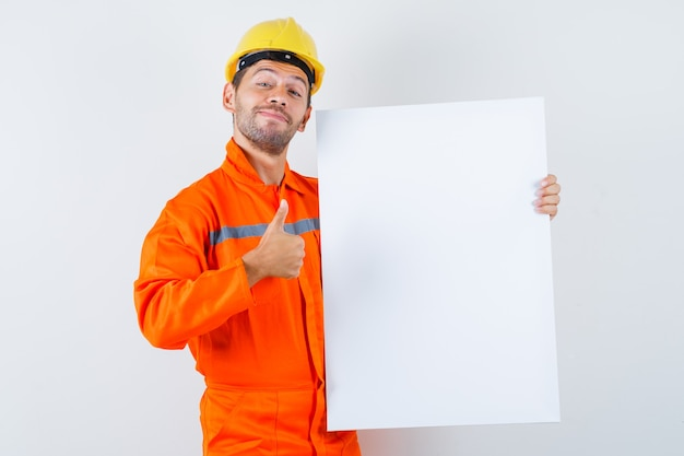 Junger arbeiter in der uniform, die leere leinwand hält, daumen hoch zeigt und fröhlich aussieht.