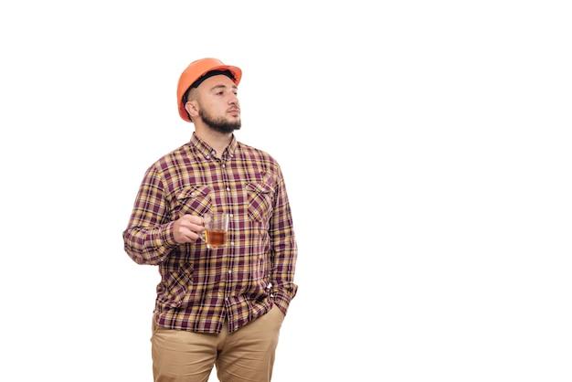 Junger arbeiter in einem orangefarbenen helm hält eine tasse tee, lokalisierten weißen hintergrund