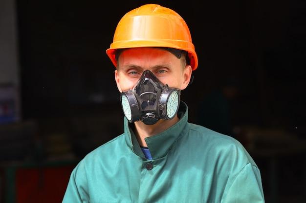 Junger arbeiter in schutzhelm und atemschutzmaske