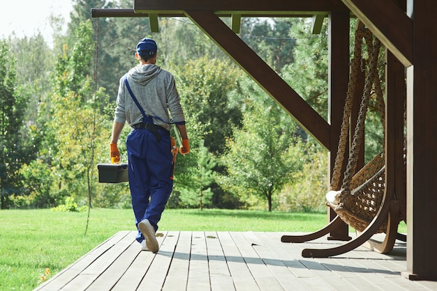 Junger arbeiter in uniform, der mit werkzeugkasten spaziert, nachdem er reparaturarbeiten im cottage-haus durchgeführt hat?
