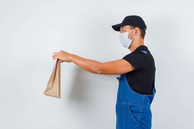 Junger arbeiter in uniform, maske, die papiertüte liefert und vorsichtig schaut.