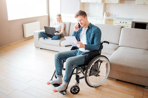 Junger arbeiter mit behinderung im zimmer. ein stück papier halten und telefonieren. junge frau sitzen hinten auf der couch mit laptop. tageslicht. paar.