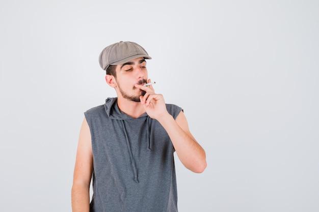 Junger arbeiter raucht zigarette und hält sie in grauem t-shirt und mütze und sieht ernst aus