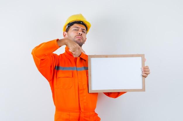 Junger arbeiter zeigt auf leeren rahmen in uniform, helm und sieht zuversichtlich aus.