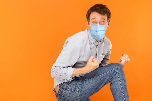 Junger arbeitermann mit chirurgischer medizinischer maske steht und feiert seinen sieg