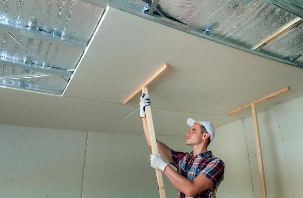 Junger arbeitnehmer in den schutzarbeitshandschuhen, die hölzerne halter für trockenmauer verschobene decke am metallrahmen reparieren.