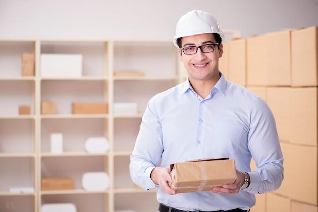 Junger arbeitnehmer in der post, die pakete beschäftigt