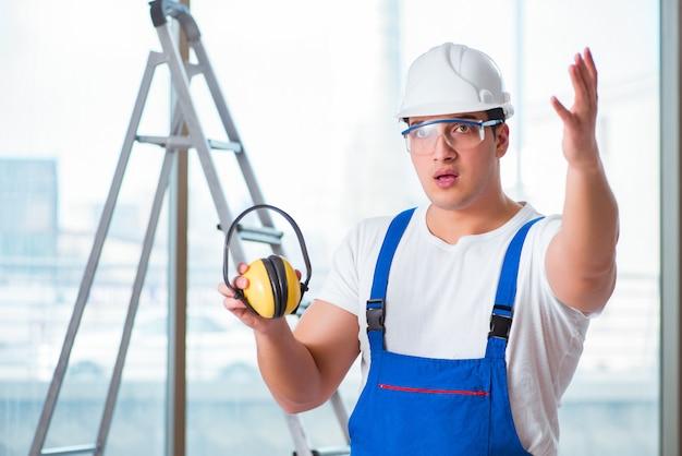 Junger arbeitnehmer mit den geräuschen, die kopfhörer annullieren